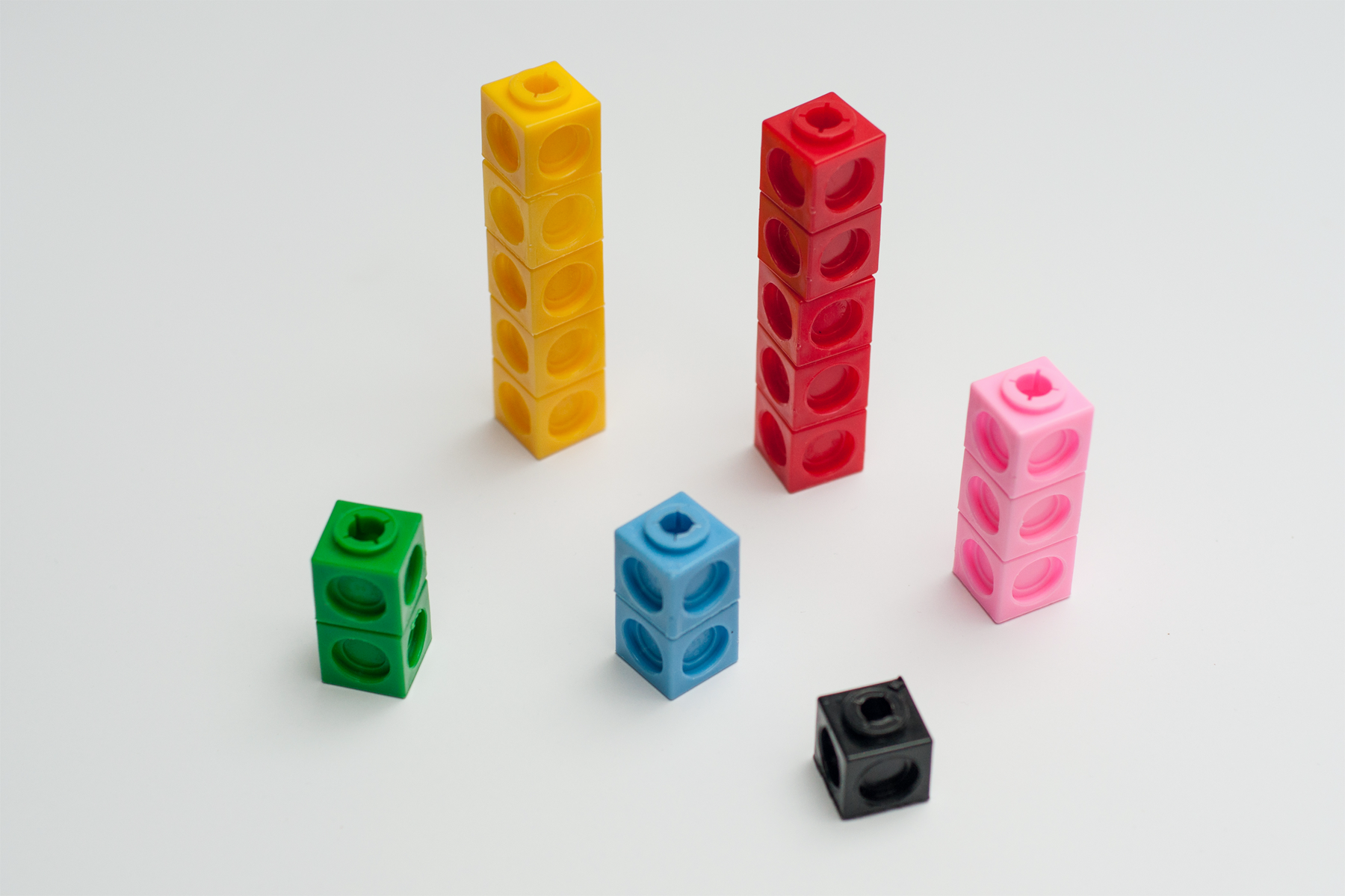 """A diagram shows a collection of snap cubes arranged by color. The collection contains 2 green, 5 yellow, 5 red, 3 pink, 2 blue, and 1 black."""