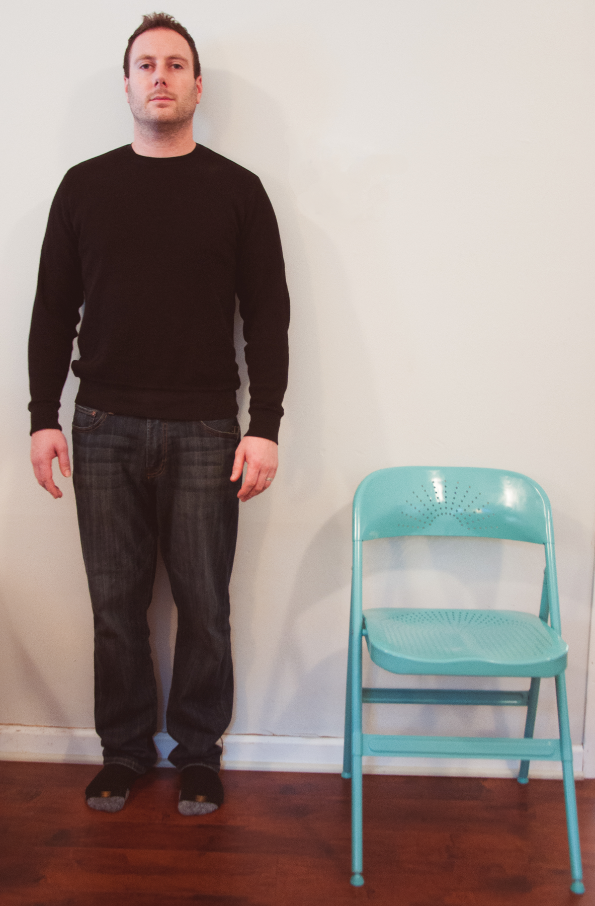A picture of a man standing next to a folding chair. The top of the folding chair comes up to the man's hip.