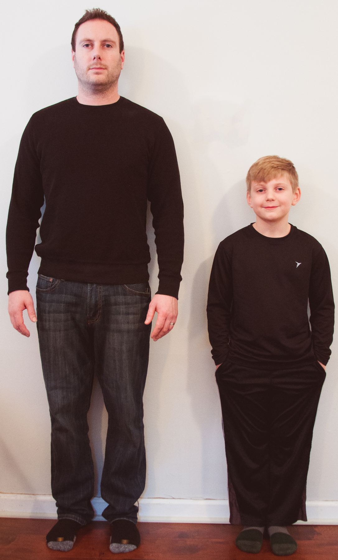 A picture of a man and boy standing next to each other. The top of the boy's head comes up to the chest of the man.